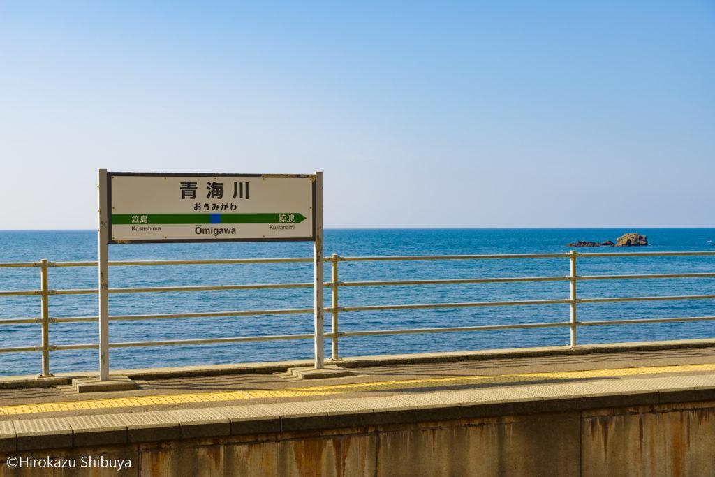 昼下がりの青海川駅の駅名票と日本海
