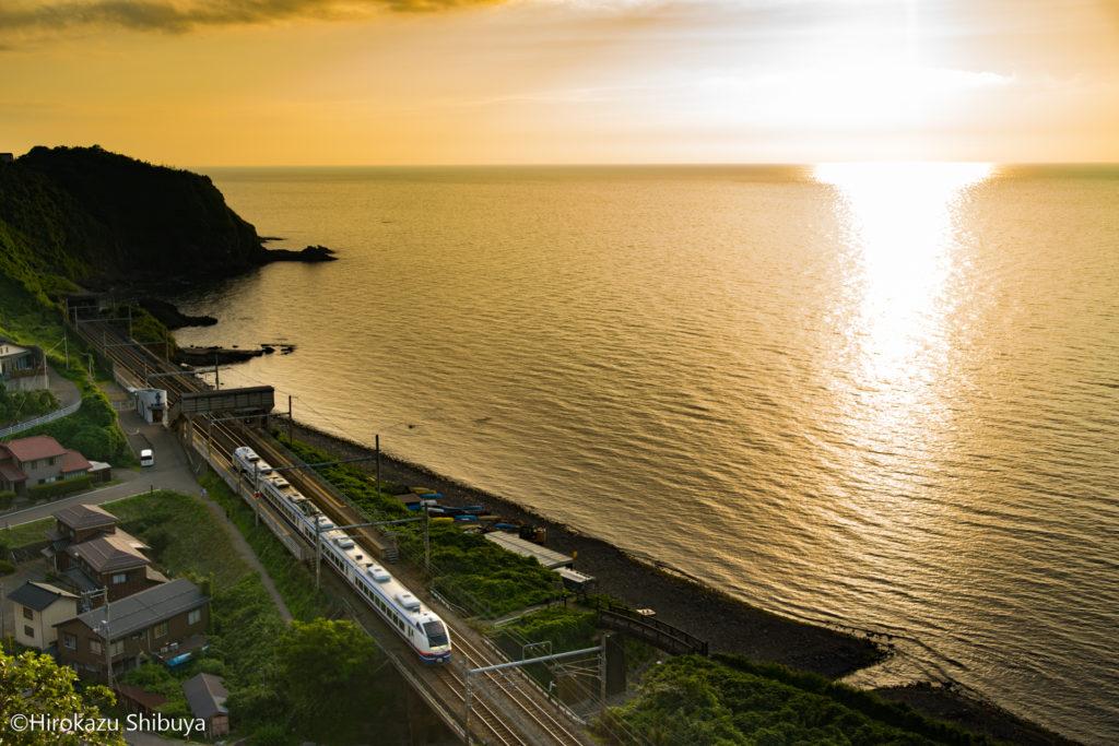 夕暮れ時の青海川駅を通過する特急しらゆき号