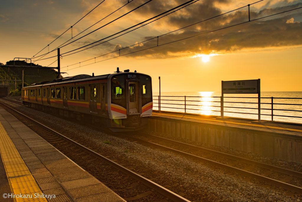 夕暮れ時の青海川駅に滑り込むE129系